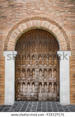 Arched entrance of a medieval palace with carved wooden door. - stock photo