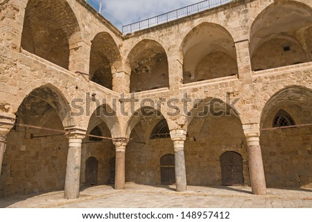 Arched gallery of Khan al-Umdan viewed from paved courtyard. Old city of Acre, Israel.  - stock photo