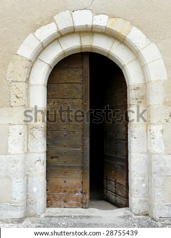 Arched medieval church door with stone lintel - stock photo