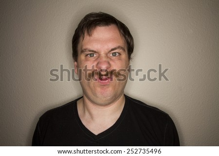 Arched mustached man not looking very happy - stock photo