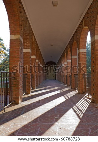Arched walkway on the campus of the College of William and Mary in Williamsburg, Virginia, with slanting rays of the morning sun vertical