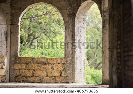 arched window and arched door in an unfinished house of limestone - stock photo