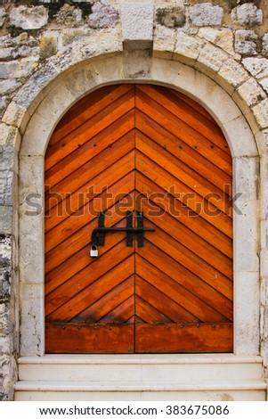 Arched wooden door - stock photo