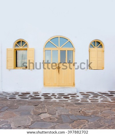 Arched wooden yellow door and windows on the whitewashed building. - stock photo