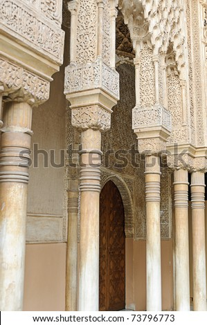 """Arches and columns in the """"Patio de los Leones"""" in the Nasrid Palace (Palacio Nazaries) of the Alhambra, Granada, Spain - stock photo"""