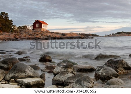 Archipelago in morning light. A distant red cottage built on the rock. Stones on the beach in the foreground - stock photo