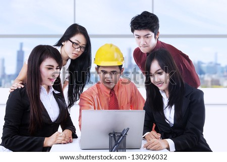 Architect and business people discussing something on a laptop in the office