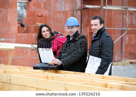 Architect and clients visiting site - stock photo