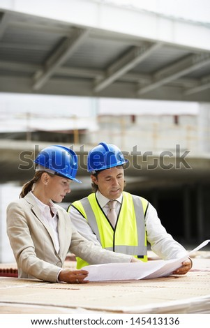 Architect and construction manager reading blueprint at site - stock photo
