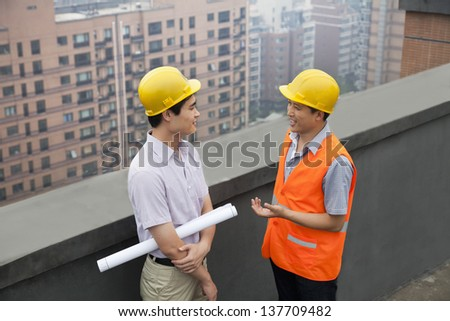 Architect And Construction Worker Talking On Rooftop