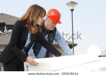 Architect and engineer review plans at a construction site. - stock photo