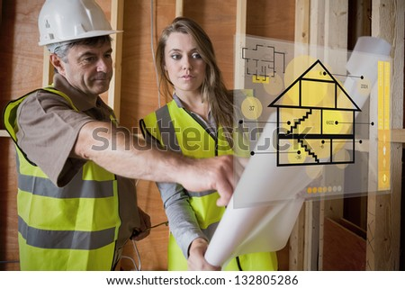 Architect and foreman consulting the plans on interface hologram - stock photo