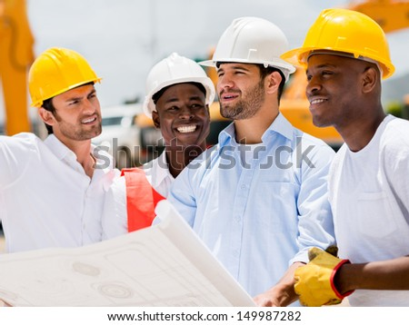Architect at a building site looking at blueprints with a group of workers - stock photo