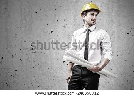 Architect at construction site holding plans in front of a concrete wall - stock photo