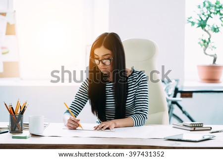 Architect at work. Beautiful young Asian woman in glasses drafting at blueprints while sitting at her working place - stock photo