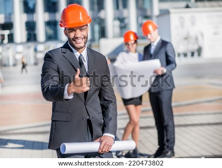 Architect at work. Smiling African architect holding blueprints in hand and showing thumbs up while standing on the construction site with his colleagues in the background - stock photo