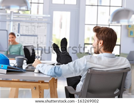 Architect designing with computer feet up on desk at modern office. - stock photo