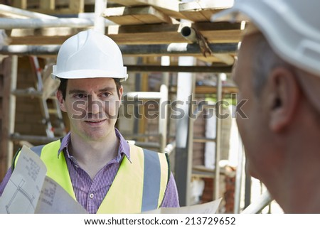 Architect Discussing Plans With Builder - stock photo