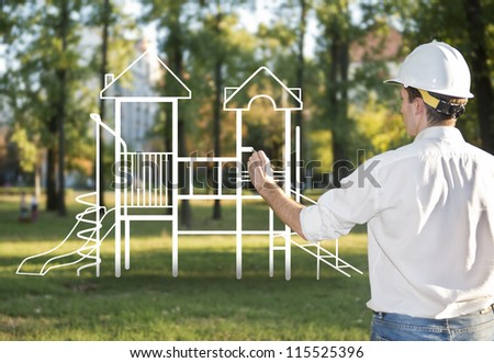 Architect drawing a playground for children in park - stock photo