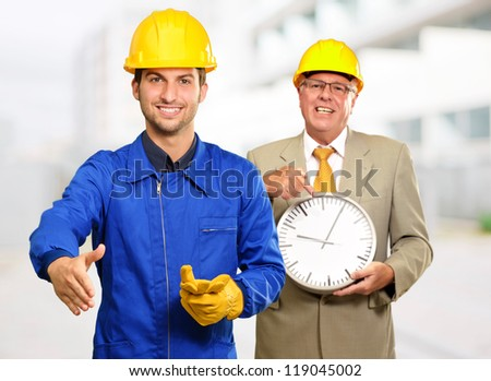 Architect Gesturing In Front Of Engineer Holding Clock, Outdoors - stock photo