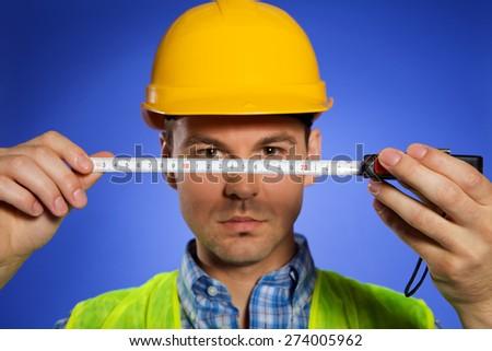 Architect in hardhat holding tape measure - stock photo