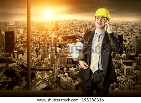 Architect in protective helmet speaking by phone - stock photo
