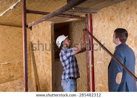 Architect in Suit Jacket Watching Construction Worker in Hard Hat Taking Measurements of Door Frame with Level Inside Unfinished New Home - stock photo