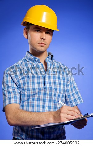 Architect in yellow hardhat writing on clipboard - stock photo