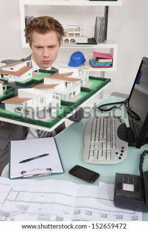 Architect inspecting model housing - stock photo