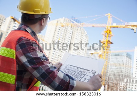 Architect looking at a blueprint outdoors at a construction site