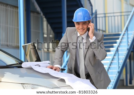 Architect looking at plans on a car bonnet - stock photo