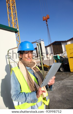 Architect on building site using electronic tablet - stock photo