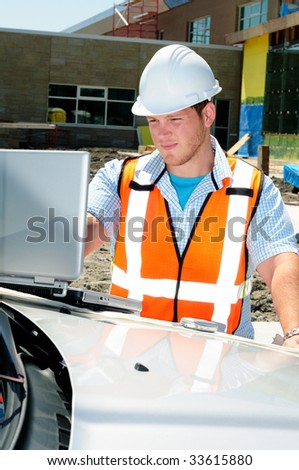 Architect On Site Using A Computer And Mobile Cellphone To Keep Connected - stock photo
