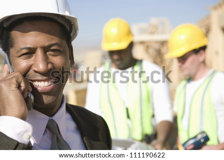 Architect phoning at a construction site - stock photo