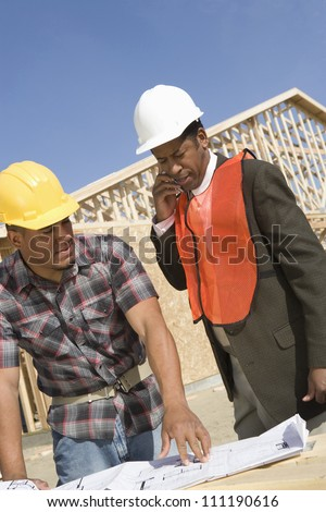 Architect phoning with co-worker standing by at construction site - stock photo