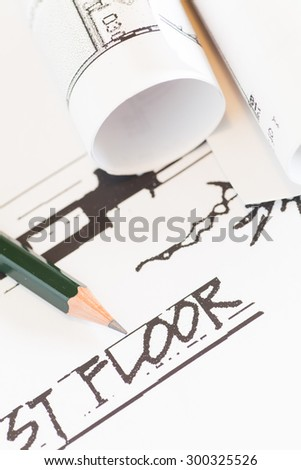 Architect rolls and plans construction project drawing   - stock photo