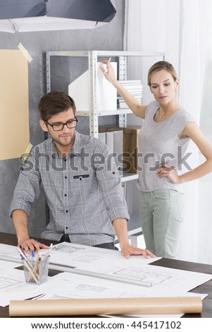 Architect sitting beside desk drawing a project, woman standing next to a regale at modern office