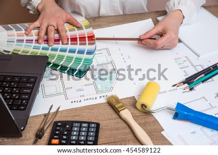 Architect sketching a construction project with laptop, color palette and work tools