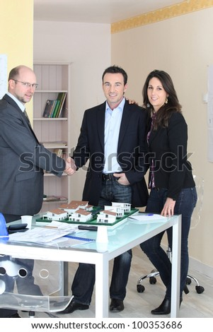 Architect stood with young couple concluding deal - stock photo