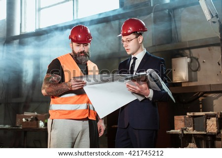 Good Architect The Suit And Helmet And Foreman Builder In Overalls And With A  Tattoo Compare Their