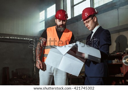 Architect the suit and helmet and foreman Builder in overalls and with a tattoo compare their drawing of a construction project with a work object - stock photo