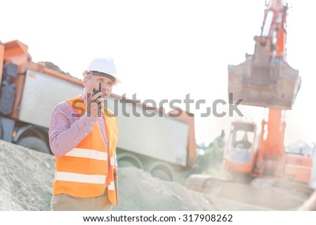 Architect using walkie-talkie while working at construction site - stock photo