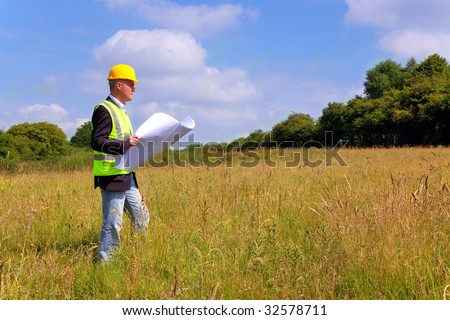 Architect wearing site safety gear and holding plans surveying a new building plot - stock photo
