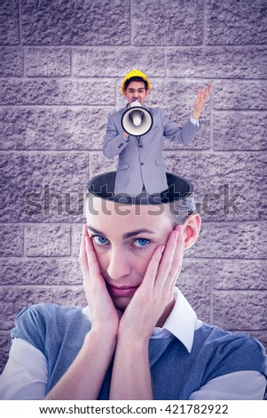 Architect with hard hat shouting with a megaphone against image of a wall - stock photo