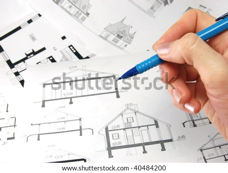 Architect with pencil and drawings of house - stock photo