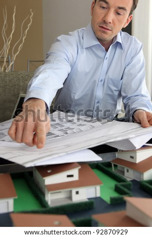 Architect with plans and  model - stock photo