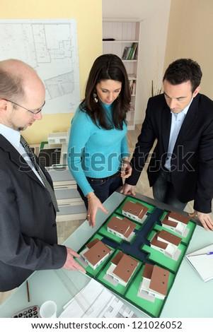 Architect with prospective buyers - stock photo