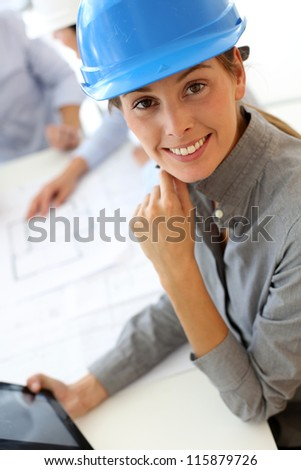 Architect with security helmet using electronic tablet - stock photo