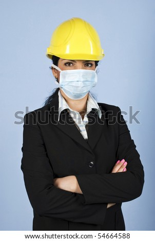 Architect woman with helmet and protective mask standing with hands folded and looking you,concept of protection from  ilness at work - stock photo