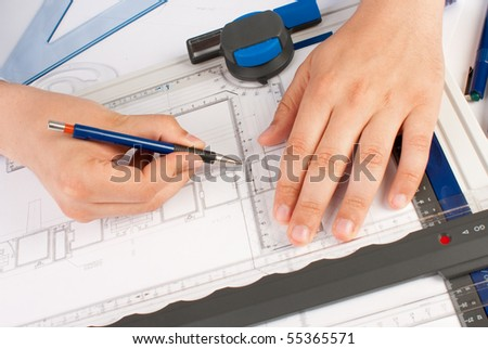 Architect working on architectural plans in the office - stock photo
